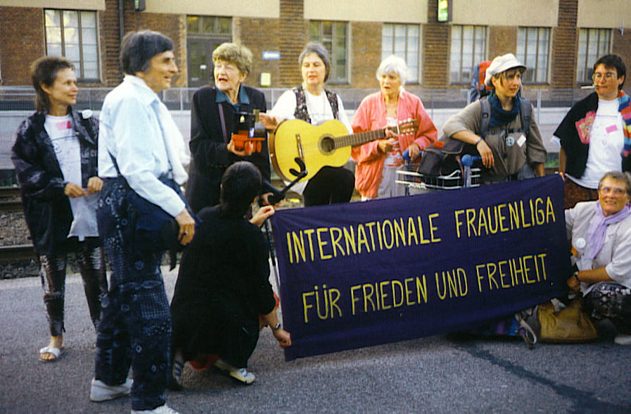 Stock photo from 1995. Women behind a WILPF banner on a train station. One with a guitar.