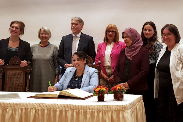 Photo of Rasha Yarhum signing a book.