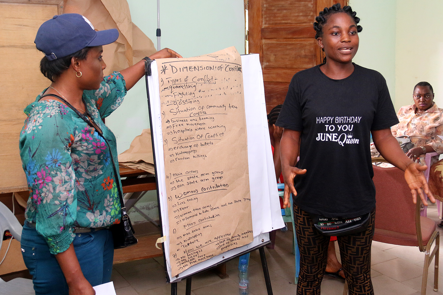 Two women standing next to a flip chart. On flip chart notes. Title on notes: Dimension of Conflict.