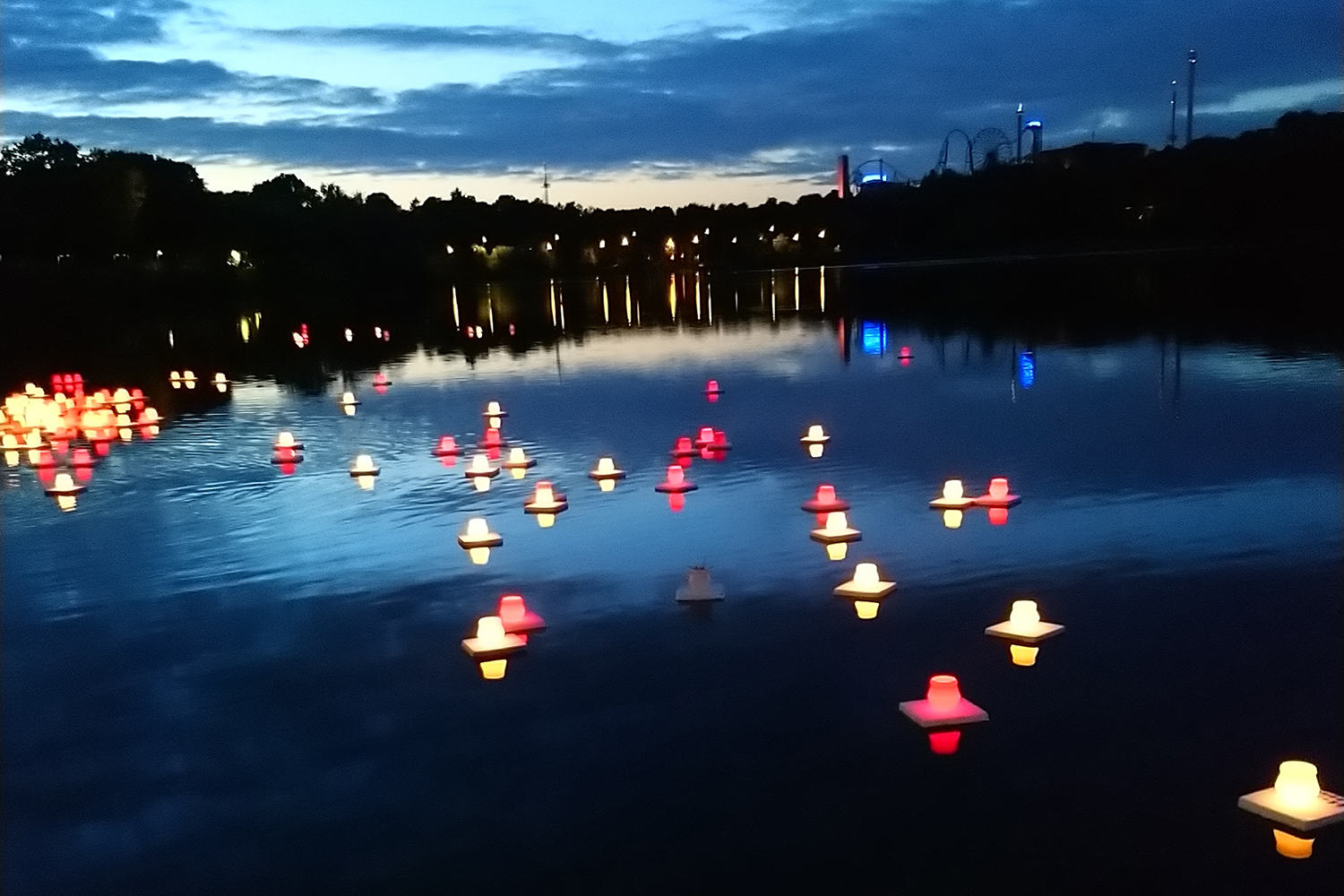 Photo of lanterns on water. A city is seen in the background. It is evening.