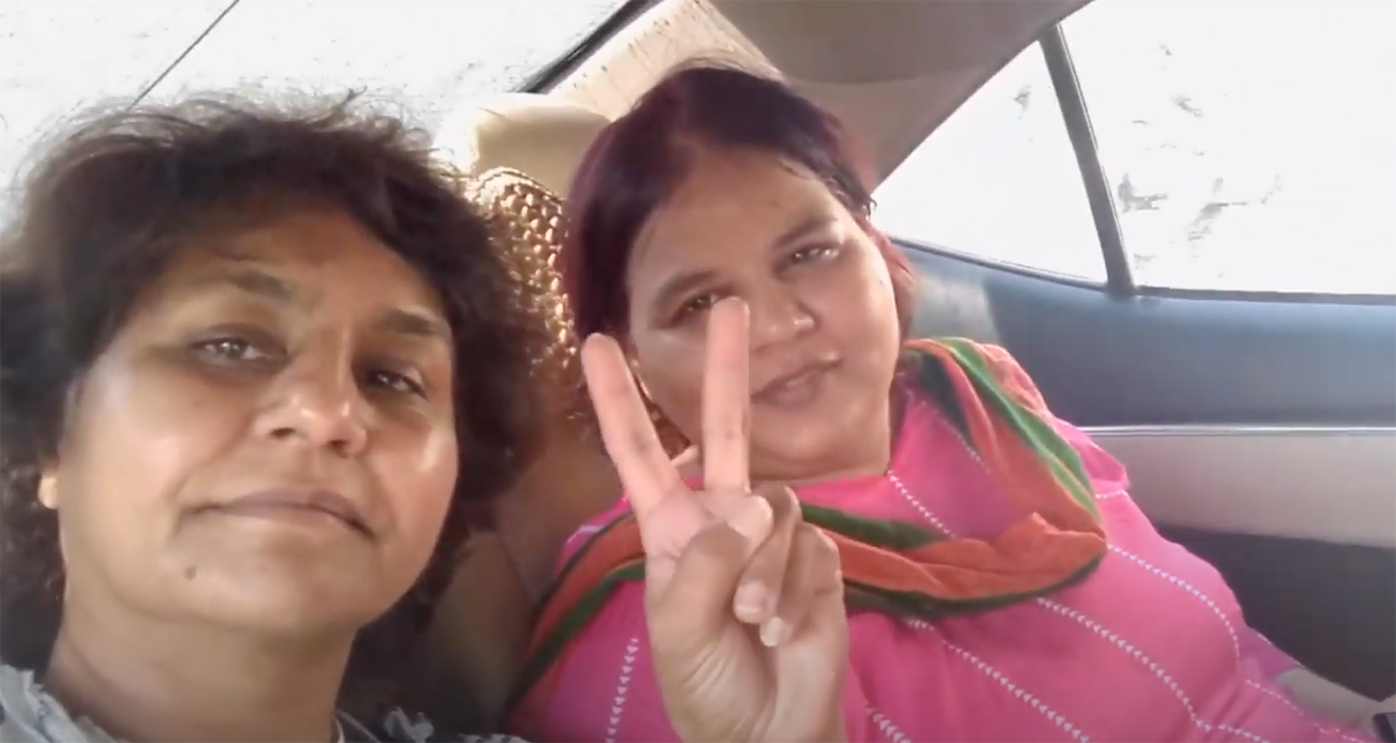 Two women in car. One making the peace-sign with her hand.