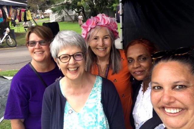 5 women smile at camera.