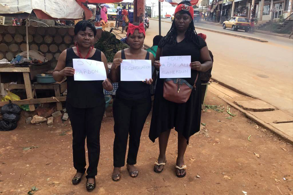Three women dressed in black clothes and with red accessories. Each holds an A4 white paper with the texts 1) SVP Pardon 2) et reconciliation 3) pour la paix au Cameroun