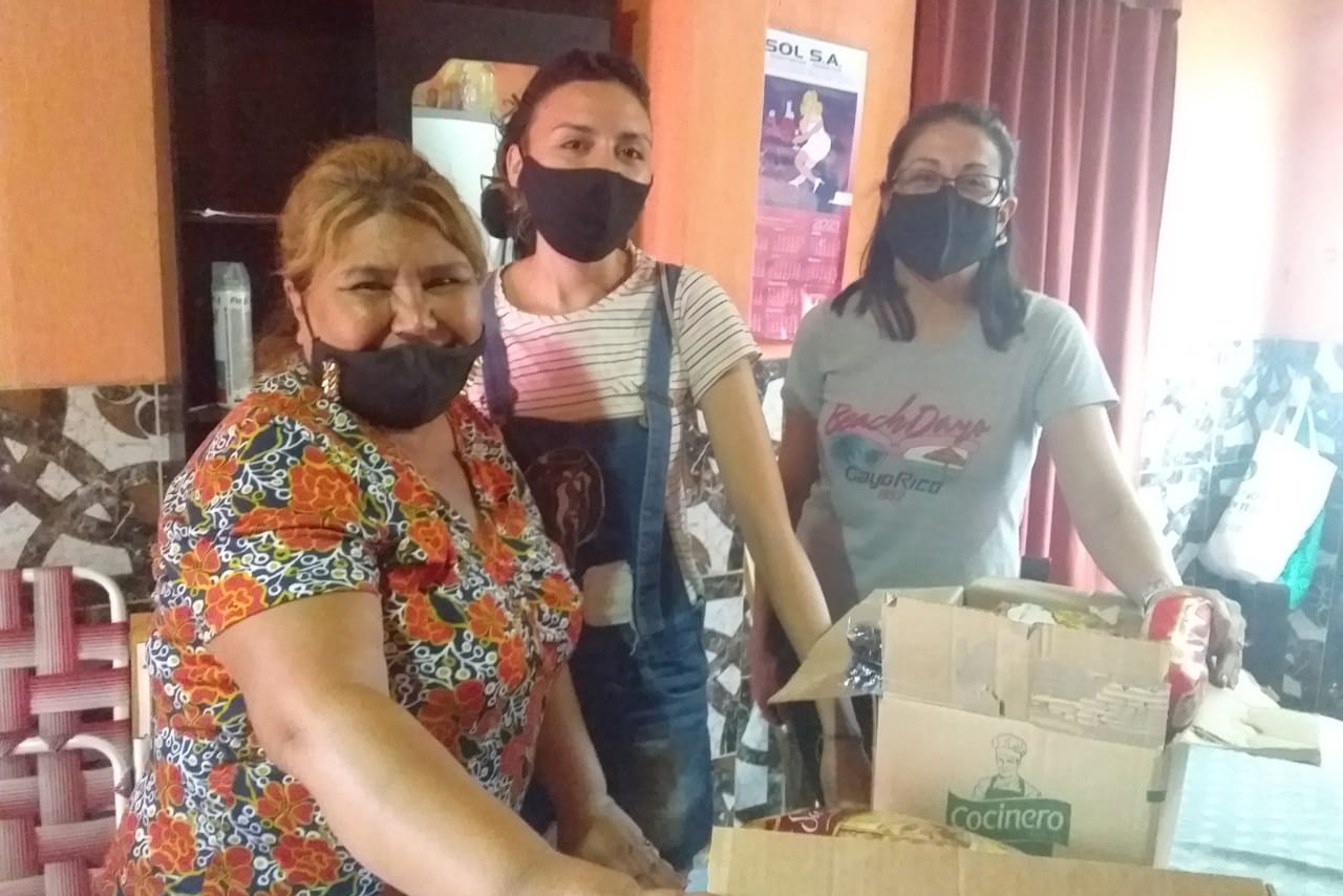 3 women stands behind carton boxes. All wear masks. Smiling eyes.